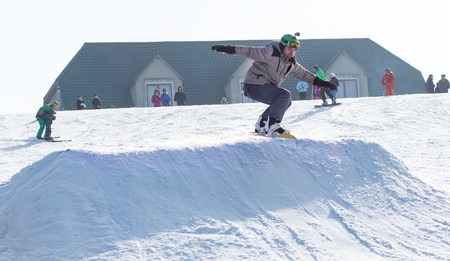 CHERKASSY, UKRAINE - February 23, 2017: Snowboard CUP, rider jumping on mountains. Extreme snowboard freeride sport.