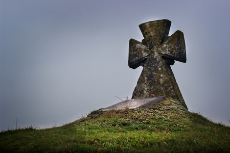 grave on the hill. Old stone cross. Green grass. Фото со стока - 93268788