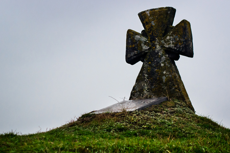 grave on the hill. Old stone cross. Green grass Фото со стока - 93379131
