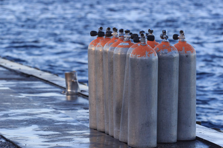 Air Tanks for Scuba Diving in a wooden platform near the diving club Maldives white sand beach. Beautiful sunset.