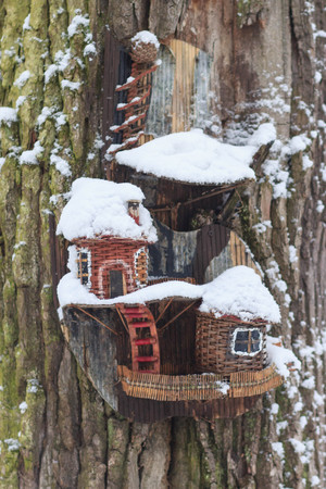 Red barn birdhouse covered in snow with snow covered trees blurred in background