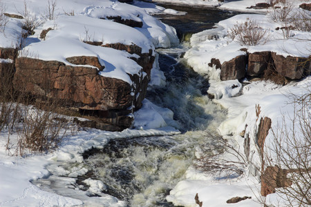 Frozen fast mountain river in winter. Spring melting of ice, springtime thaw