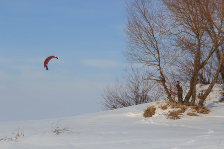 Landscape: Snowkiting skier on snowy mountains on a sunny day