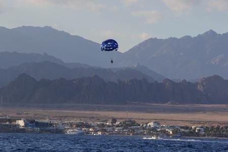 Sharm El Sheikh, Egypt - February 3 2018: Tourists are extremely entertained flying parasailing. Редакционное