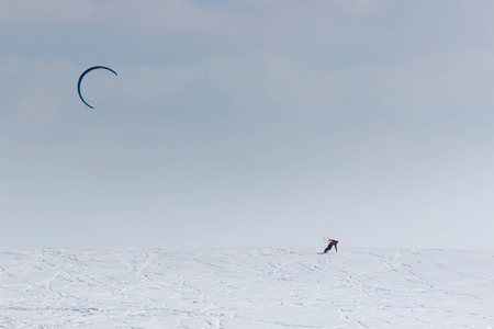 A snowboarder with a kite rides on a frozen lake on free ride