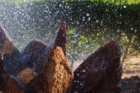 Scenic waterfall view with sparkling drops of water splashing on the stones.