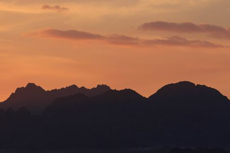 Sunset over the mountains. Orange sky.