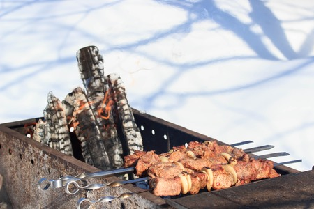 Outdoors winter barbecue party with a person wearing knitted woollen gloves cooking sausages over hot coals in a BBQ, close up view