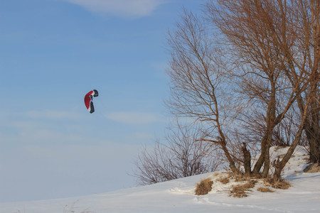 Landscape: Snowkiting skier on snowy mountains on a sunny day, sport where the kite trains the person and thanks to the wind go back to the mountains, Фото со стока