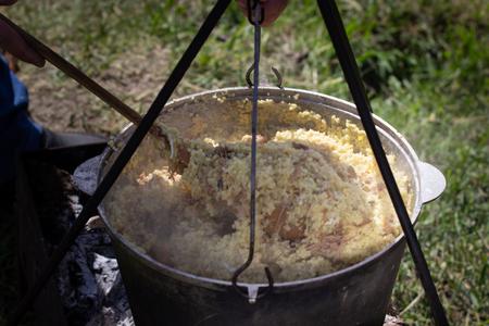 In the black cauldron on the fire prepare porridge. Фото со стока
