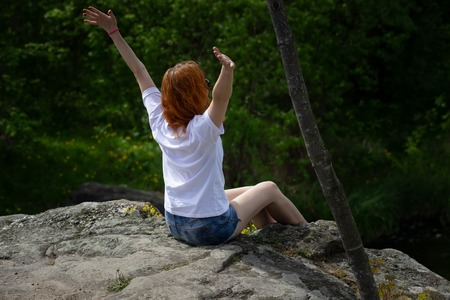 On the edge of a rocky cliff a girl raises his hands to heaven as a sign of freedom or victory and in the background a fantastic landscape.