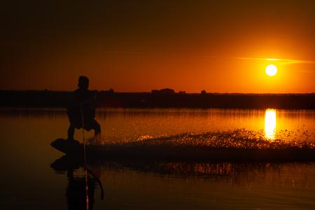 Wakeboarder making tricks on sunset