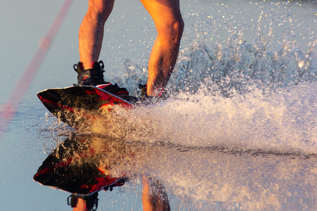 Mens feet on a wakeboard in water.guy sitting by the river and is preparing to go wake boarding Фото со стока