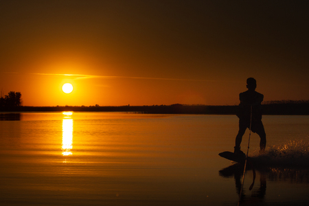 wakeboard, athlete silhouette on sunset background Фото со стока
