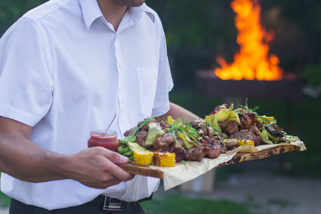 Waiter is offering grilled meat and vegetables.