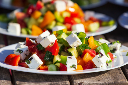 Greek salad of fresh cucumber, tomato, sweet pepper, lettuce, red onion, feta cheese and olives with olive oil. Healthy food
