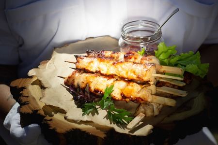 Chicken skewers with slices of apples and chili sauce on a wooden slice Фото со стока