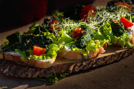 Close up bruschetta with proschuto, tomato, parmesan cheese and arugula.