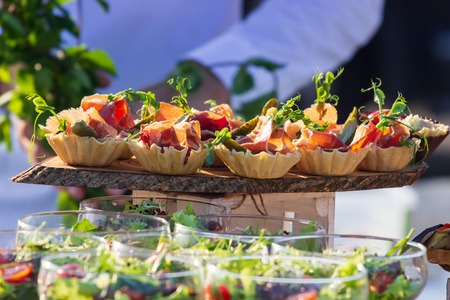exquisite beautiful serve prosciutto in baskets on a wooden slice. Catering