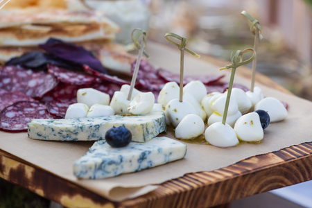 Cheese plates served with grapes, jam, figs, crackers and nuts on a wooden background Фото со стока - 105943690