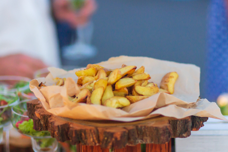 French fried potatoes in metal basket on wooden background. Фото со стока - 105944069