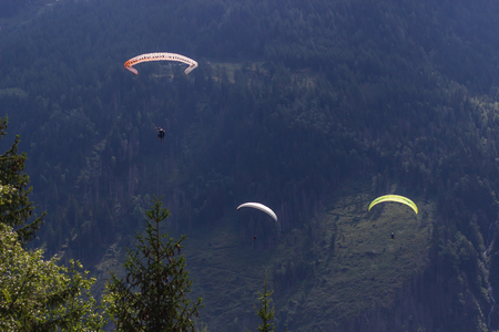 Paragliding flying over Mont Blanc Massif, in the background are Aiguilles du Chamonix, Alps, Chamonix, France