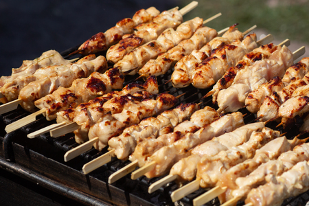 Grilled chicken on bamboo skewers, close up view. Catering
