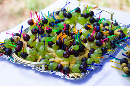 Canape with cheese, grape and olive.