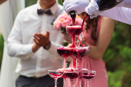 A pyramid of champagne glasses with a rose petals.