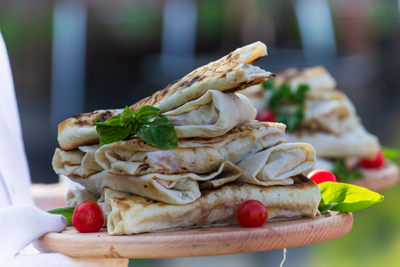 Shawarma chicken roll in a pita with fresh vegetables, cream sauce and french fries on wooden background Фото со стока