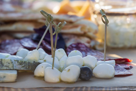 Cheese plates served with grapes, jam, figs, crackers and nuts on a wooden background