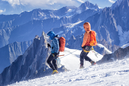 A group of mountaineers climbs to the top of a snow-capped mountain. Фото со стока