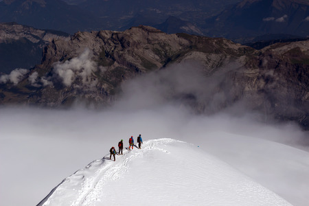 A group of mountaineers climbs to the top of a snow-capped mountain. 版權商用圖片