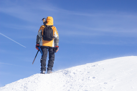 Tied climbers climbing mountain with snow field tied with a rope with ice axes and helmets.