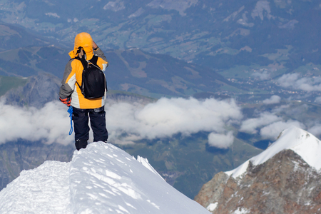 Tied climbers climbing mountain with snow field tied with a rope with ice axes and helmets. Фото со стока - 110366770
