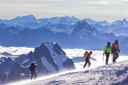 A group of mountaineers climbs to the top of a snow-capped mountain. Zdjęcie Seryjne