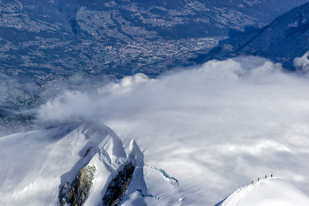 Mountaineer reaches the top of a snowy mountain in a sunny winter day. Reklamní fotografie