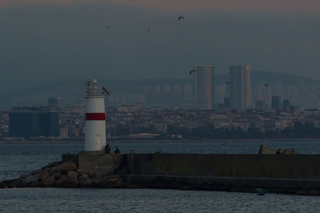Seaside view with water waves, rocks, a lot of birds and lighthouse in eminonu, istanbul, turkey