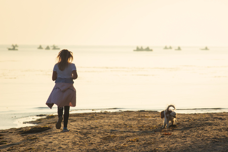 Woman and dog running free on beach on golden sunset. Fitness girl and her pet working out together