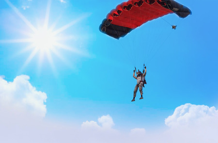 A red parachute in a blue sky on a sunny day. Фото со стока