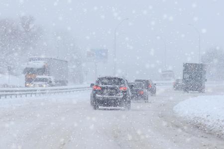 Fahrendes Auto auf verschneiter Winterstraße zwischen gefrorenem Wald nach Graupel. Kaltes Wetter, Schneesturm, schlechte Sicht, rutschige Straße. Moskauer Gebiet.