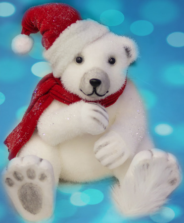 White Bear with christmas hat on a blue background. Stock Photo