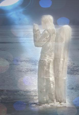 Icy sculpture of frozen angel in winter lake.