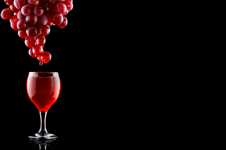 Wine glass and red grapes with drops on blak backgound. Space fot text menu.