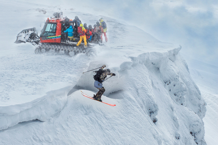 A group of freeriders arrived at the top of the mountain on a snowmobile. One skier jumps off a cliff.