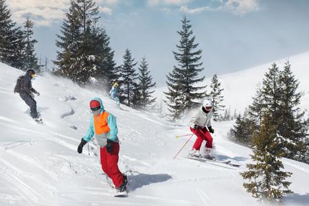 Groep gelukkige vrienden snowboarders en skiërs rijden op de skipiste en plezier hebben. Stockfoto