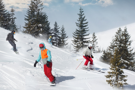 Group of happy friends snowboarders and skiers riding on ski slope and having fun. Reklamní fotografie