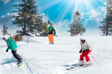 Group of happy friends snowboarders and skiers riding on ski slope and having fun. Foto de archivo