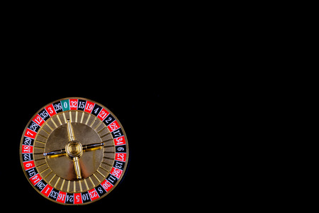 Roulette table in casino, with many games and slots, roulette wheel in the foreground. Black background for text Reklamní fotografie