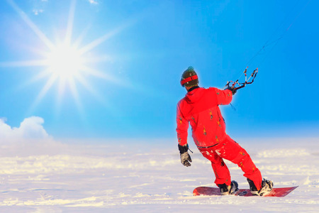 Kite surfer ride on snowboard. Snowkiting in the snow on frozen lake. Winter sun day. Space for text Stok Fotoğraf